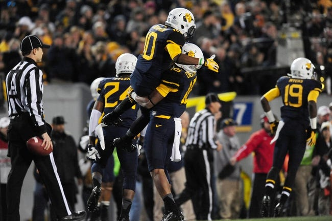 Nov 9, 2013; Morgantown, WV, USA; West Virginia Mountaineers wide receiver Jordan Thompson (10) celebrates with cornerback Terrell Chestnut (16) during the game against the Texas Longhorns at Milan Puskar Stadium. Mandatory Credit: Evan Habeeb-USA TODAY Sports
