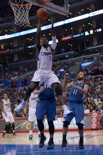 Nov 11, 2013; Los Angeles, CA, USA; Los Angeles Clippers guard Darren Collison (2) is defended by Minnesota Timberwolves forward Kevin Love (42) and guard Jose Barea (11) at Staples Center. The Clippers defeated the Timberwolves 109-107. Mandatory Credit: Kirby Lee-USA TODAY Sports