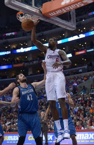 Nov 11, 2013; Los Angeles, CA, USA; Los Angeles Clippers center DeAndre Jordan (6) dunks the ball as Minnesota Timberwolves forward Kevin Love (42) watches at Staples Center. The Clippers defeated the Timberwolves 109-107. Mandatory Credit: Kirby Lee-USA TODAY Sports