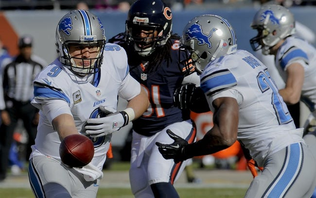 Nov 10, 2013; Chicago, IL, USA;  Detroit Lions quarterback Matthew Stafford (9)  hands off to running back Reggie Bush (21) during the game against the Bears at Soldier Field. Mandatory Credit: Matt Marton-USA TODAY Sports
