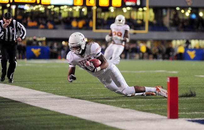 Nov 9, 2013; Morgantown, WV, USA; Texas Longhorns wide receiver Marcus Johnson (7) dives out of bounds during the game against the West Virginia Mountaineers at Milan Puskar Stadium. Mandatory Credit: Evan Habeeb-USA TODAY Sports