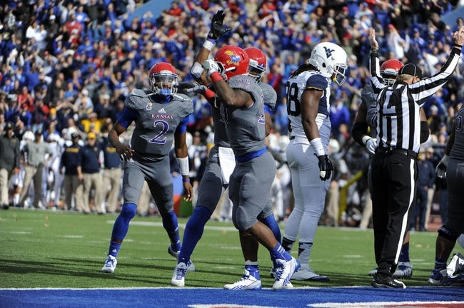 Nov 16, 2013; Lawrence, KS, USA; Kansas Jayhawks running back James Sims (29) is congratulated by quarterback Montell Cozart (2) and wide receiver Justin McCay (19) after scoring a touchdown against the West Virginia Mountaineers in the first half at Memorial Stadium. Mandatory Credit: John Rieger-USA TODAY Sports
