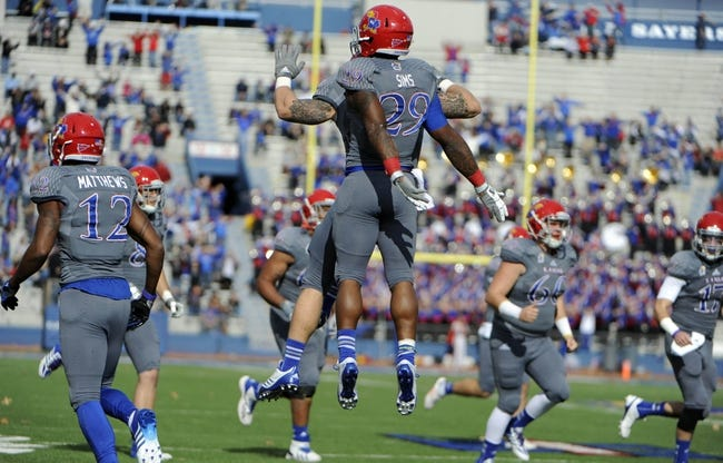 Nov 16, 2013; Lawrence, KS, USA; Kansas Jayhawks running back James Sims (29) is congratulated by fullback T.J. Semke (35) after scoring a touchdown against the West Virginia Mountaineers in the first half at Memorial Stadium. Mandatory Credit: John Rieger-USA TODAY Sports