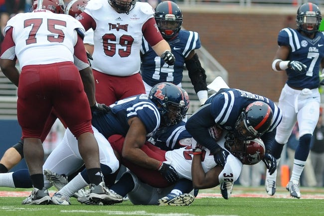 Nov 16, 2013; Oxford, MS, USA; Troy Trojans running back Brandon Burks (32) is tackled by  Mississippi Rebels defensive end Robert Nkemdiche (5) during the first half at Vaught-Hemingway Stadium. Mandatory Credit: Justin Ford-USA TODAY Sports