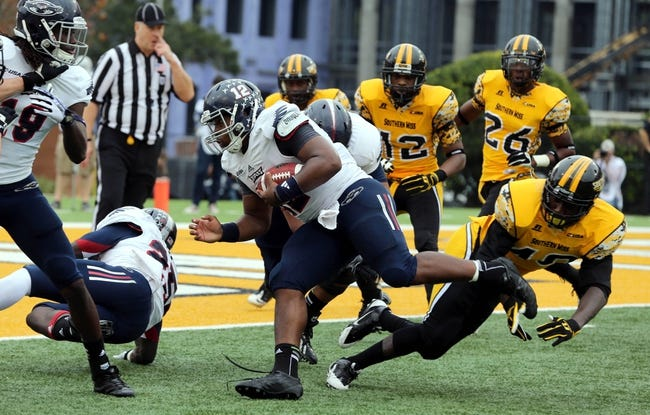 Nov 16, 2013; Hattiesburg, MS, USA; Florida Atlantic Owls quarterback Jaquez Johnson (12) scores a touchdown on a 5-yard run against the Southern Miss Golden Eagles during the first half at M.M. Roberts Stadium. Mandatory Credit: Chuck Cook-USA TODAY Sports