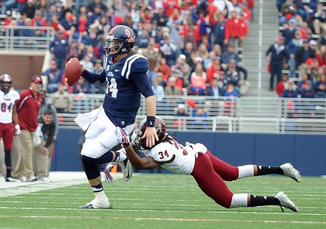 Nov 16, 2013; Oxford, MS, USA; Mississippi Rebels quarterback Bo Wallace (14) is brought down by Troy Trojans cornerback Ethan Davis (34) during the first half at Vaught-Hemingway Stadium. Mandatory Credit: Justin Ford-USA TODAY Sports