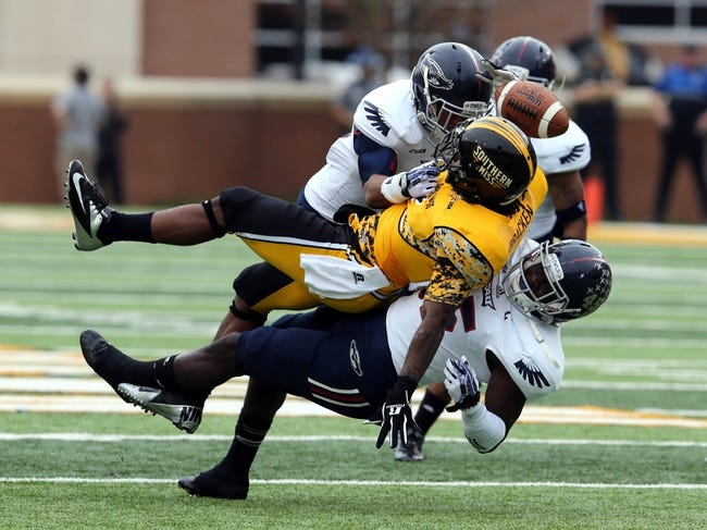 Nov 16, 2013; Hattiesburg, MS, USA; Southern Miss Golden Eagles running back Tyre Bracken (3) loses the football after being hit by Florida Atlantic Owls linebacker Andrae Kirk (45) and safety Jeremy McKnight (26) during the first quarter at M.M. Roberts Stadium. It was ruled that Bracken's forward progress was stopped before the fumble. Mandatory Credit: Chuck Cook-USA TODAY Sports