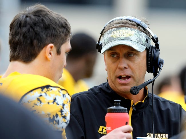 Nov 16, 2013; Hattiesburg, MS, USA; Southern Miss head coach Todd Monken talks with quarterback Nick Mullens (14) on the sidelines of their game against the Florida Atlantic Owls in the first half at M.M. Roberts Stadium. Mandatory Credit: Chuck Cook-USA TODAY Sports