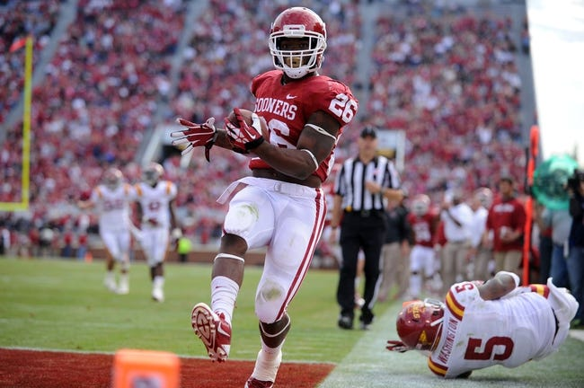 Nov 16, 2013; Norman, OK, USA; Oklahoma Sooners running back Damien Williams (26) scores a touchdown while being pursued by Iowa State Cyclones Jacques Washington (5) in the second half at Gaylord Family - Oklahoma Memorial Stadium. Mandatory Credit: Mark D. Smith-USA TODAY Sports
