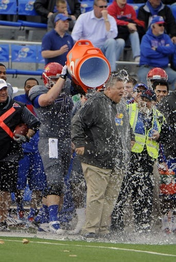 Nov 16, 2013; Lawrence, KS, USA; Kansas Jayhawks offensive linesman Gavin Howard (70) pours water over Kansas Jayhawks head coach Charlie Weis late in the game against the West Virginia Mountaineers at Memorial Stadium. Kansas won the game 31-19. Mandatory Credit: John Rieger-USA TODAY Sports