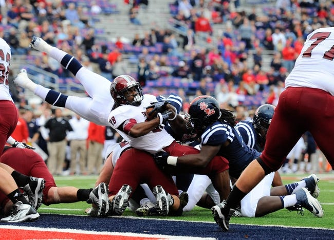 Nov 16, 2013; Oxford, MS, USA; Troy Trojans running back Daron White (28) is tackled by Mississippi Rebels defensive tackle Herbert Moore (99) while scoring a touchdown during the fourth quarter at Vaught-Hemingway Stadium. Mississippi Rebels beat the Troy Trojans 51-21. Mandatory Credit: Justin Ford-USA TODAY Sports