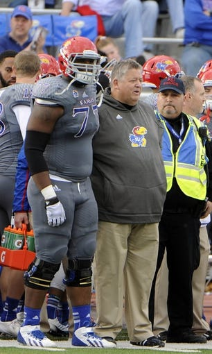 Nov 16, 2013; Lawrence, KS, USA; Kansas Jayhawks offensive linesman Aslam Sterling (77) congratulates  head coach Charlie Weis (right) in the final minutes against the West Virginia Mountaineers at Memorial Stadium. Kansas won the game 31-19. Mandatory Credit: John Rieger-USA TODAY Sports