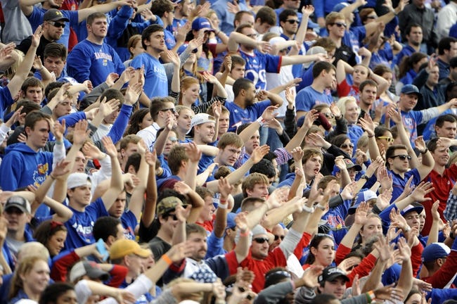 Nov 16, 2013; Lawrence, KS, USA; Kansas Jayhawks fans cheer after a touchdown against the West Virginia Mountaineers in the second half at Memorial Stadium. Kansas won the game 31-19. Mandatory Credit: John Rieger-USA TODAY Sports