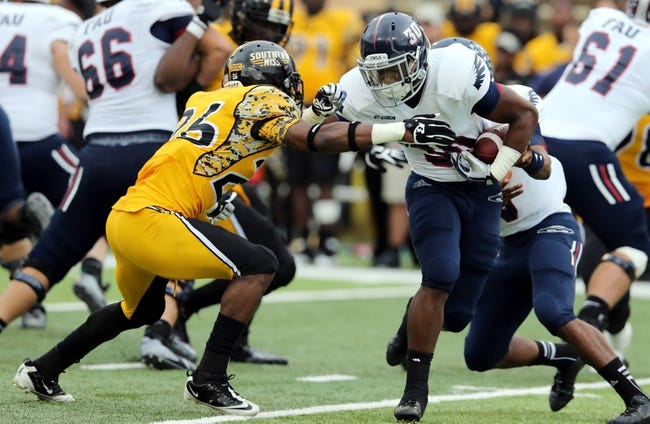 Nov 16, 2013; Hattiesburg, MS, USA; Florida Atlantic Owls running back Jeremy Gaskins (30) runs with the ball as Southern Miss Golden Eagles defensive back Debarriaus Miller (26) defends during the second half at M.M. Roberts Stadium. Florida Atlantic won 41-7. Mandatory Credit: Chuck Cook-USA TODAY Sports