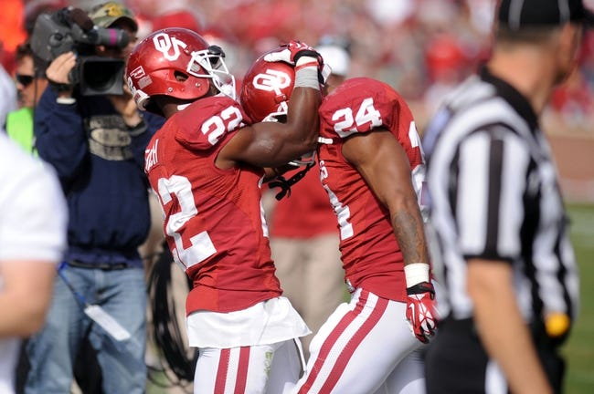 Nov 16, 2013; Norman, OK, USA; Oklahoma Sooners running back Brennan Clay (24) celebrates a touchdown with Sooners running back Roy Finch (22) against the Iowa State Cyclones in the second half at Gaylord Family - Oklahoma Memorial Stadium. Mandatory Credit: Mark D. Smith-USA TODAY Sports