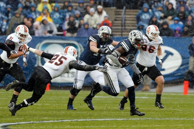 Nov 16, 2013; Provo, UT, USA; Brigham Young Cougars running back Jamaal Williams (21) breaks a tackle from Idaho State Bengals defensive back Tanner Davis (25) and runs down the field to score a touchdown at Lavell Edwards Stadium. Mandatory Credit: Chris Nicoll-USA TODAY Sports
