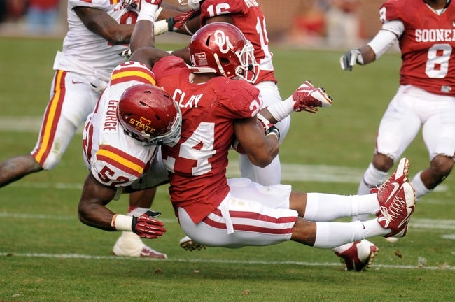 Nov 16, 2013; Norman, OK, USA; Oklahoma Sooners running back Brennan Clay (24) is tackled by Iowa State Cyclones linebacker Jeremiah George (52) in the second half at Gaylord Family - Oklahoma Memorial Stadium. Mandatory Credit: Mark D. Smith-USA TODAY Sports