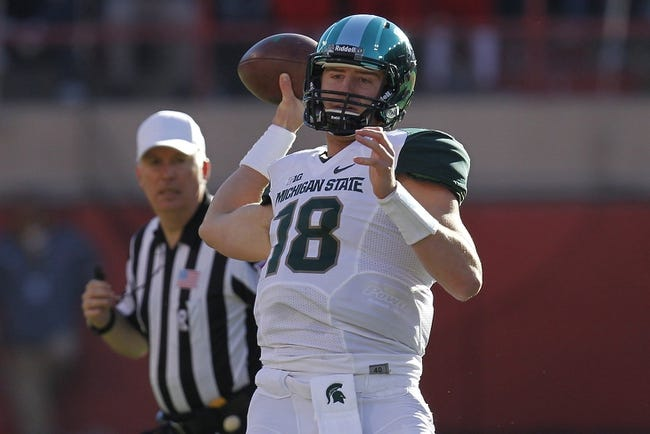 Nov 16, 2013; Lincoln, NE, USA; Michigan State Spartans quarterback Connor Cook (18) throws against the Nebraska Cornhuskers in the first quarter at Memorial Stadium. Mandatory Credit: Bruce Thorson-USA TODAY Sports