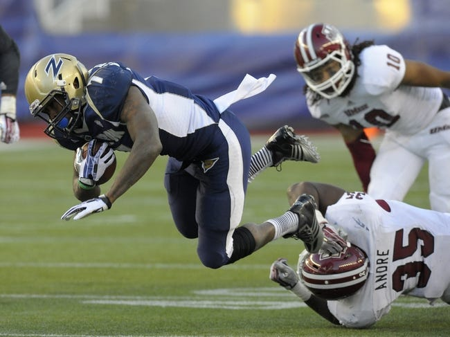 Nov 16, 2013; Foxborough, MA, USA; Akron Zips running back Jawon Chisholm (7) is tackled by Massachusetts Minutemen defensive lineman Stanley Andre (35) during the second half at Gillette Stadium. Mandatory Credit: Bob DeChiara-USA TODAY Sports