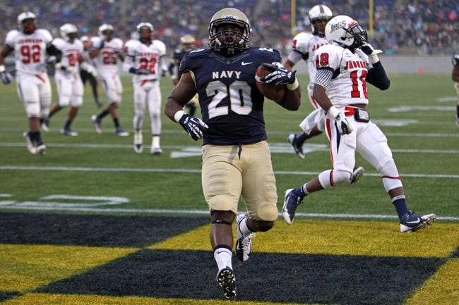Nov 16, 2013; Annapolis, MD, USA; Navy Midshipmen slotback Darius Staten (20) scores a first half rushing touchdown against the South Alabama Jaguars at Navy Marine Corps Memorial Stadium. Mandatory Credit: Mitch Stringer-USA TODAY Sports