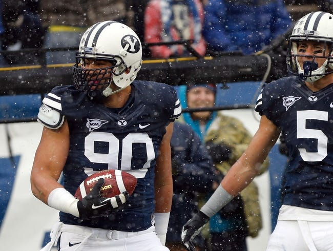 Nov 16, 2013; Provo, UT, USA; Brigham Young Cougars defensive lineman Bronson Kaufusi (90) celebrates in the end zone after intercepting a Idaho State Bengals pass and running it into the end zone during the second quarter at Lavell Edwards Stadium. Mandatory Credit: Chris Nicoll-USA TODAY Sports