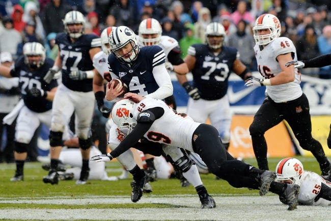 Nov 16, 2013; Provo, UT, USA; Brigham Young Cougars quarterback Taysom Hill (4) is tackled by Idaho State Bengals defensive back Cody Sorensen (29) during the second quarter at Lavell Edwards Stadium. Mandatory Credit: Chris Nicoll-USA TODAY Sports