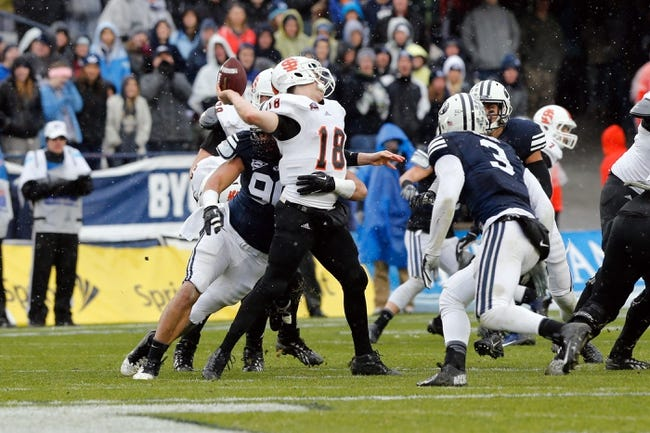 Nov 16, 2013; Provo, UT, USA; Brigham Young Cougars defensive lineman Bronson Kaufusi (90) hits Idaho State Bengals quarterback Justin Arias (18) as Arias tries to pass the ball during the second quarter at Lavell Edwards Stadium. Mandatory Credit: Chris Nicoll-USA TODAY Sports
