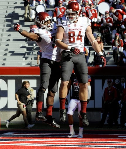 Nov 16, 2013; Tucson, AZ, USA; Washington State Cougars wide receiver River Cracraft (84) celebrates with running back Marcus Mason (35) after scoring a touchdown during the third quarter against the Arizona Wildcats at Arizona Stadium. The Cougars beat the Wildcats 24-17. Mandatory Credit: Casey Sapio-USA TODAY Sports