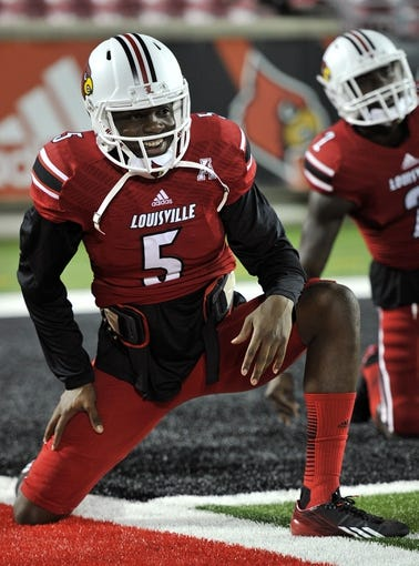 Nov 16, 2013; Louisville, KY, USA; Louisville Cardinals quarterback Teddy Bridgewater (5) warms up before the first quarter of play against the Houston Cougars at Papa John' Cardinal Stadium. Mandatory Credit: Jamie Rhodes-USA TODAY Sports