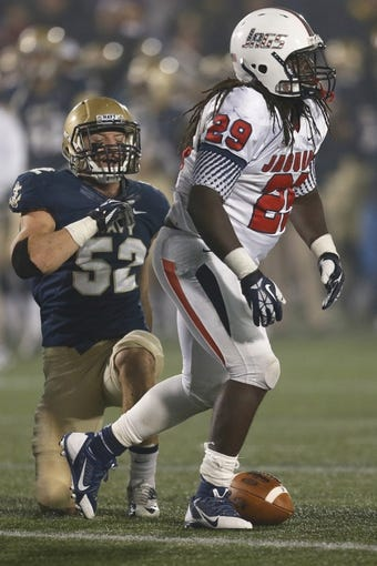 Nov 16, 2013; Annapolis, MD, USA; Navy Midshipmen linebacker DJ Sargenti (52) tackles South Alabama Jaguars running back Kendall Houston (29) at Navy Marine Corps Memorial Stadium. Mandatory Credit: Mitch Stringer-USA TODAY Sports