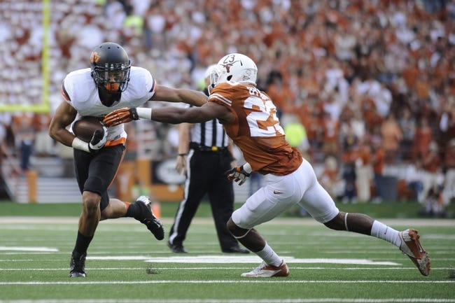 Nov 16, 2013; Austin, TX, USA; Oklahoma State Cowboys wide receiver Jhajuan Seales (left) carries the ball against Texas Longhorns cornerback Carrington Byndom (23) during the third quarter at Darrell K Royal-Texas Memorial Stadium. Oklahoma State beat Texas 38-13. Mandatory Credit: Brendan Maloney-USA TODAY Sports