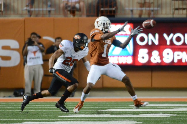 Nov 16, 2013; Austin, TX, USA; Texas Longhorns wide receiver Mike Davis (1) makes a catch against Oklahoma State Cowboys cornerback Tyler Patmon (26) during the fourth quarter at Darrell K Royal-Texas Memorial Stadium. Oklahoma State beat Texas 38-13. Mandatory Credit: Brendan Maloney-USA TODAY Sports