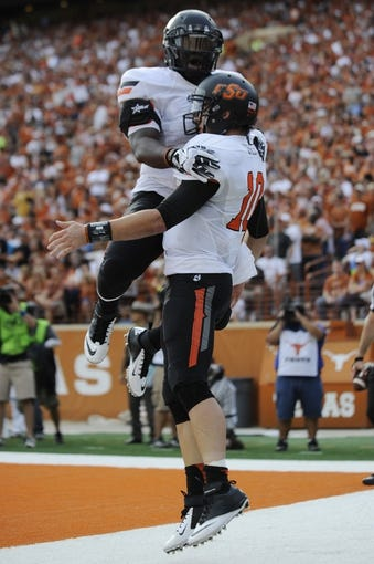 Nov 16, 2013; Austin, TX, USA; Oklahoma State Cowboys quarterback Clint Chelf (10) and running back Rennie Childs (l) celebrate after scoring a touchdown against the Texas Longhorns during the first quarter at Darrell K Royal-Texas Memorial Stadium. Oklahoma State won 38-13. Mandatory Credit: Brendan Maloney-USA TODAY Sports