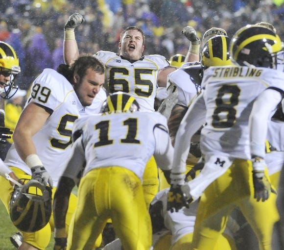 Nov 16, 2013; Evanston, IL, USA; Michigan Wolverines offensive linesman Kyle Bosch (65) and his teammates celebrate their overtime win against the Northwestern Wildcats at Ryan Field. The Michigan Wolverines defeated the Northwestern Wildcats 27-19 in triple overtime. Mandatory Credit: David Banks-USA TODAY Sports