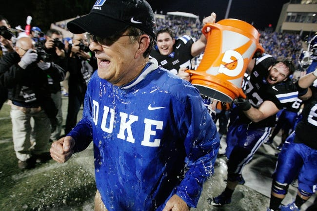 Nov 16, 2013; Durham, NC, USA; Duke Blue Devils head coach David Cutcliffe gets doused by players long snapper Thomas Hennessy (57) and offensive tackle Perry Simmons (72) as the Blue Devils beat the Miami Hurricanes 48-30 at Wallace Wade Stadium. Mandatory Credit: Mark Dolejs-USA TODAY Sports