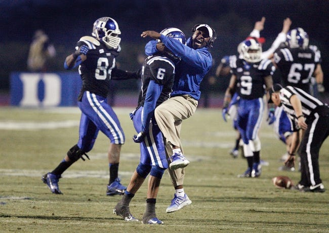 Nov 16, 2013; Durham, NC, USA; Duke Blue Devils Associate Head Coach Scottie Montgomery jumps in the arms of cornerback Ross Cockrell (6) after Cockrell broke up a Miami Hurricanes pass at Wallace Wade Stadium. Mandatory Credit: Mark Dolejs-USA TODAY Sports