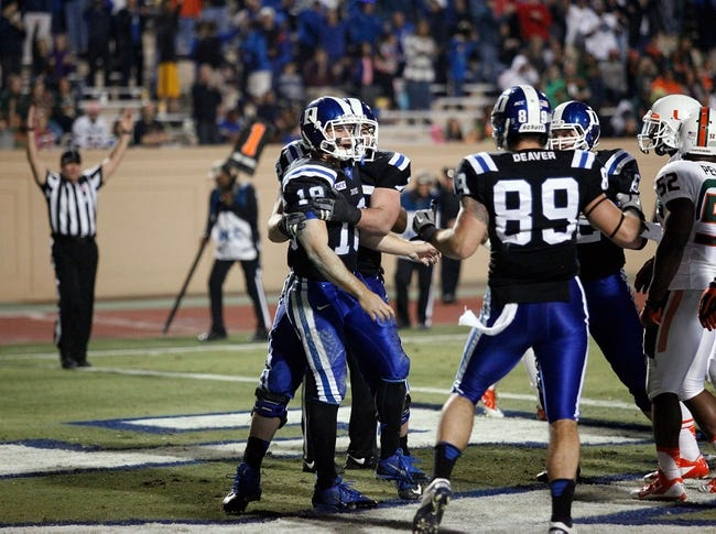 Nov 16, 2013; Durham, NC, USA; Duke Blue Devils offensive tackle Perry Simmons (72) and tight end Braxton Deaver (89) celebrate with quarterback Brandon Connette (18) after Connette scored a touchdown against the Miami Hurricanes at Wallace Wade Stadium. Mandatory Credit: Mark Dolejs-USA TODAY Sports