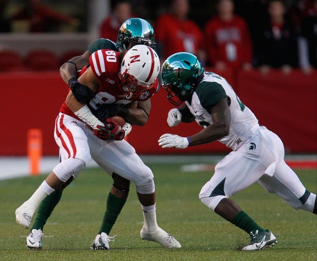 Nov 16, 2013; Lincoln, NE, USA; Nebraska Cornhuskers receiver Kenny Bell (80) catches a pass and is tackled by Michigan State Spartans defenders Darqueze Dennard (31) and RJ Williamson (26) in the third quarter at Memorial Stadium. Michigan State won 41-28. Mandatory Credit: Bruce Thorson-USA TODAY Sports