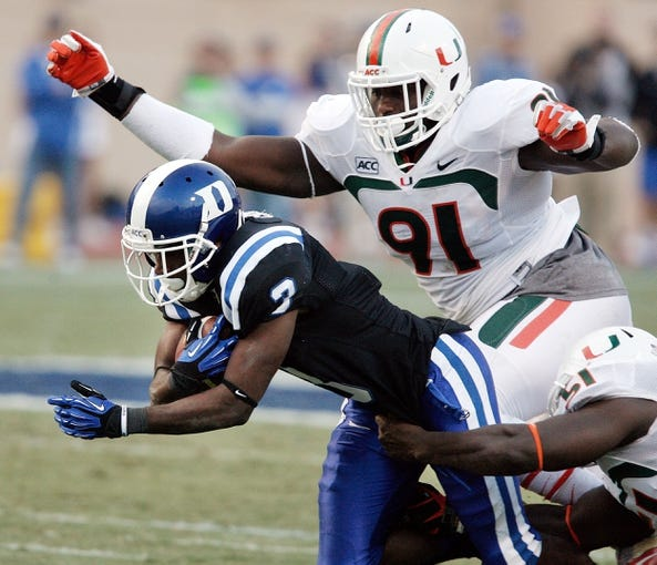 Nov 16, 2013; Durham, NC, USA; Miami Hurricanes defensive lineman Olsen Pierre (91) defends as Duke Blue Devils wide receiver Jamison Crowder (3) runs with the ball at Wallace Wade Stadium. Mandatory Credit: Mark Dolejs-USA TODAY Sports