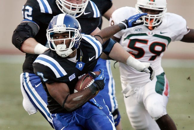 Nov 16, 2013; Durham, NC, USA; Duke Blue Devils wide receiver Jamison Crowder (3) runs with the ball past Miami Hurricanes linebacker Jimmy Gaines (59) at Wallace Wade Stadium. Mandatory Credit: Mark Dolejs-USA TODAY Sports