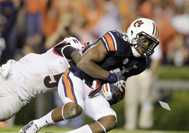 Nov 16, 2013; Auburn, AL, USA; Georgia Bulldogs cornerback Damian Swann (5) tackles Auburn Tigers receiver Ricardo Louis (5) during the second half at Jordan Hare Stadium.  The Tigers beat the Bulldogs 43-38.  Mandatory Credit: John Reed-USA TODAY Sports