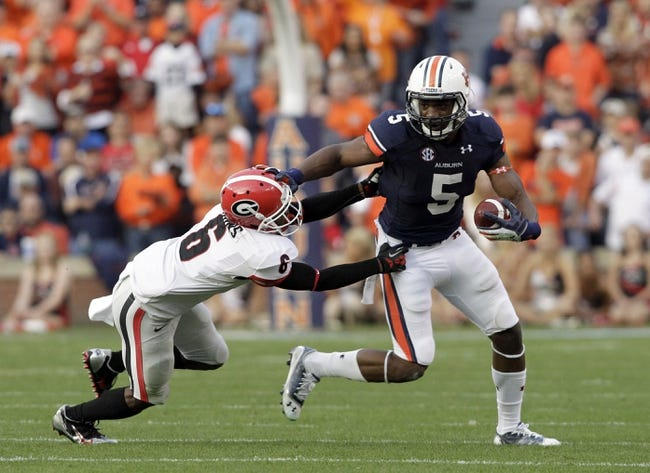 Nov 16, 2013; Auburn, AL, USA; Auburn Tigers receiver Ricardo Louis (5) avoids Georgia Bulldogs cornerback Shaq Wiggins (6) during the first half at Jordan Hare Stadium.  The Tigers beat the Bulldogs 43-38.  Mandatory Credit: John Reed-USA TODAY Sports