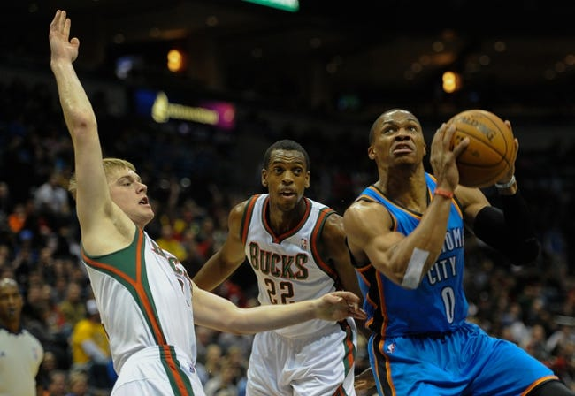 Nov 16, 2013; Milwaukee, WI, USA;  Oklahoma City Thunder guard Russell Westbrook (0) shoots against Milwaukee Bucks guard Nate Wolters (6) and forward Khris Middleton (22) in the 1st quarter at BMO Harris Bradley Center. Mandatory Credit: Benny Sieu-USA TODAY Sports