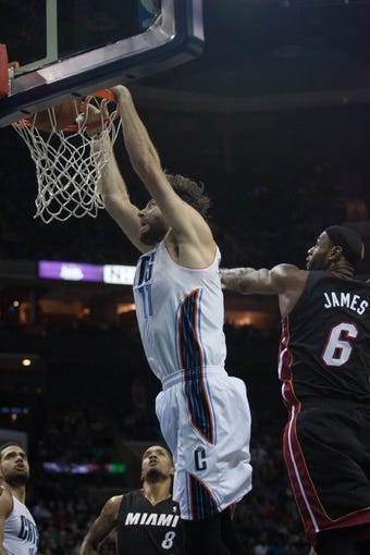 Nov 16, 2013; Charlotte, NC, USA; Charlotte Bobcats power forward Josh McRoberts (11) dunks the ball over Miami Heat small forward LeBron James (6) during the second half at Time Warner Cable Arena. Miami defeated Charlotte 97-81. Mandatory Credit: Jeremy Brevard-USA TODAY Sports