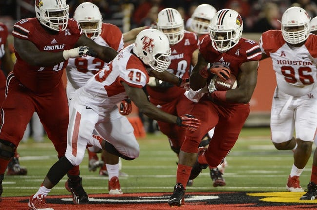 Nov 16, 2013; Louisville, KY, USA; Louisville Cardinals running back Dominique Brown (10) runs the ball against Houston Cougars linebacker Derrick Mathews (49) during the second half of play at Papa John's Cardinal Stadium. Louisville defeated Houston 20-13.  Mandatory Credit: Jamie Rhodes-USA TODAY Sports