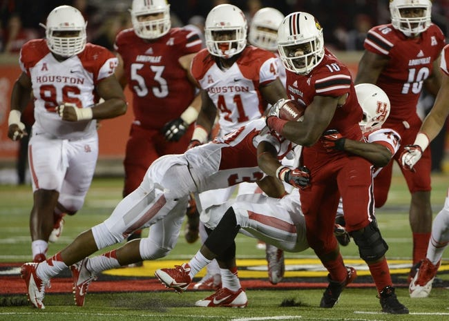 Nov 16, 2013; Louisville, KY, USA; Louisville Cardinals running back Dominique Brown (10) tries to break the tackle of Houston Cougars linebacker Derrick Mathews (49) during the second half of play at Papa John's Cardinal Stadium. Louisville defeated Houston 20-13.  Mandatory Credit: Jamie Rhodes-USA TODAY Sports