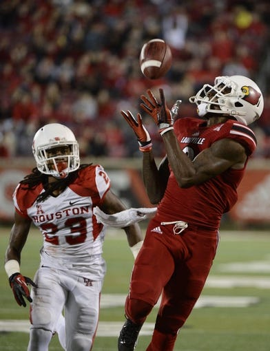 Nov 16, 2013; Louisville, KY, USA; Louisville Cardinals wide receiver DeVante Parker (9) catches a pass in front of  Houston Cougars defensive back Trevon Stewart (23) during the second half of play at Papa John's Cardinal Stadium. Louisville defeated Houston 20-13.  Mandatory Credit: Jamie Rhodes-USA TODAY Sports