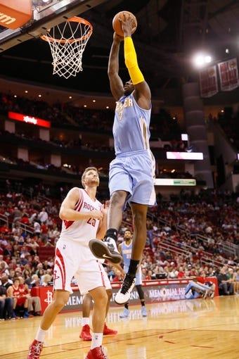 Nov 16, 2013; Houston, TX, USA; Denver Nuggets forward JJ Hickson (7) dunks as Houston Rockets forward Chandler Parsons (25) looks on during the second half at Toyota Center. The Rockets won 122-111. Mandatory Credit: Soobum Im-USA TODAY Sports