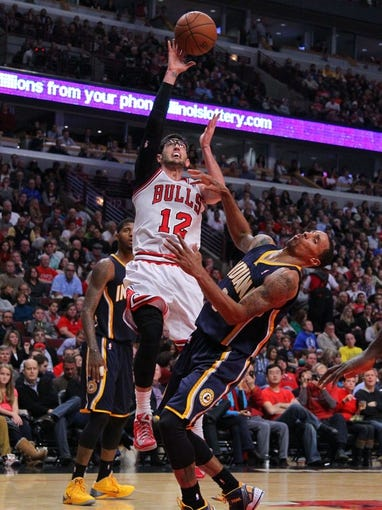 Nov 16, 2013; Chicago, IL, USA; Chicago Bulls shooting guard Kirk Hinrich (12) is called for an offensive foul against Indiana Pacers point guard George Hill (3) during the second half at  the United Center. Chicago won 110-94. Mandatory Credit: Dennis Wierzbicki-USA TODAY Sports