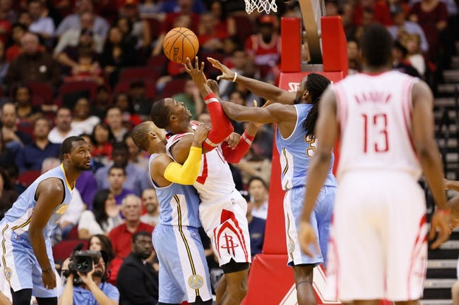 Nov 16, 2013; Houston, TX, USA; Houston Rockets center Dwight Howard (center) gets fouled while shooting against Denver Nuggets guard Randy Foye (left) during the second half at Toyota Center. The Rockets won 122-111. Mandatory Credit: Soobum Im-USA TODAY Sports